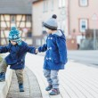 Stock Photo: Two little sibling boys walking on street in Germvillage.