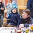 Stock Photo: Father and little son having fun on toy exposition, indoors.