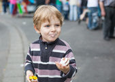 Little boy of three years eating at a funfair, outdoors — Stock Photo