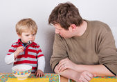 Young father and little son eating at home kitchen. — Stock Photo