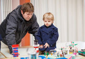 Father and little son having fun on toy exposition, indoors. — Stock Photo