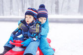 Happy family: two little twin boys having fun with snow in winte — Stock Photo