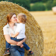 Stock Photo: Young mother and her little son having fun on yellow hay field