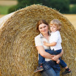 Young mother and her little son having fun on yellow hay field — Stock Photo