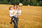 Jeune maman et deux peu jumeaux garçons s'amusant sur foin jaune — Photo