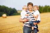 Padre de joven y dos pequeños gemelos chicos divirtiéndose en amarillo paja — Foto de Stock