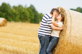Young couple in love on yellow hay field on summer evening. — Стоковое фото
