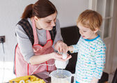 Little toddler boy and his mother having fun with baking at home — Stockfoto