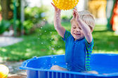 Little toddler boy having fun with splashing water in summer gar — Stockfoto