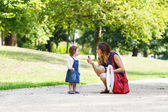 Young woman and little girl of one year walking through summer p — Stock Photo