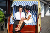 Beautiful indian bride and caucasian groom, in beach chair. — Stock Photo
