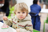 Little blond toddler boy eating ice cream iin shopping mall — Stock Photo