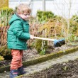 Little boy in spring with garden hoe, planting and gardening — Stok fotoğraf