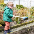 Little boy in spring with garden hoe, planting and gardening — 图库照片