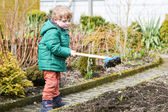 Little boy in spring with garden hoe, planting and gardening — Stock Photo