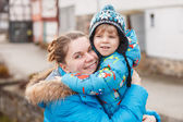 Adorable caucasian little boy and mother hugging on bridge, outd — ストック写真