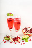 Two glasses with red pomgranate champagne, lime and mint. — ストック写真