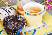 Chocolate and coconut donuts with carnival decoration. — Stock Photo