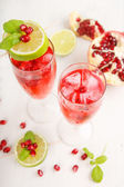 Two glasses with red pomgranate champagne, lime and mint. — Stock Photo