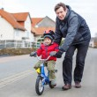 Young father teaching his 3 years old little son to ride a bike — Stock Photo
