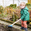 Little boy in spring with garden hoe, planting and gardening — Stock Photo #43014527
