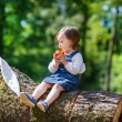 Little cute baby girl eating fruit in forest — Stock Photo