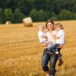 Young mother and two little twins boys having fun on yellow hay — Stock Photo
