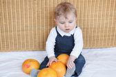 Adorable baby boy playing with oranges — Stock Photo