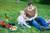 Young father helping his son with shoes on green grass — Stock Photo