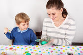 Mother And Son Decorating Easter Eggs On Table indoor. — Stock Photo