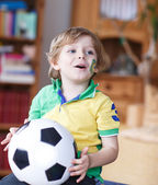 Little blond preschool boy of 4 years with football looking socc — Foto de Stock