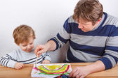 Father and little boy of two years having fun painting — Stock Photo