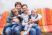 Family of four sitting on a bench in home garde — Stock Photo