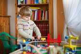 Little toddler boy playing with wooden railway, indoors — Стоковое фото
