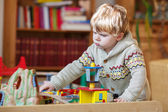 Little toddler boy playing with wooden railway, indoors — Stok fotoğraf