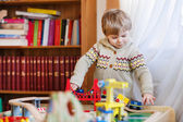 Little toddler boy playing with wooden railway, indoors — Stock fotografie