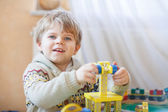 Little toddler boy playing with wooden toy, indoors — Стоковое фото