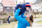 Adorable caucasian little boy and mother hugging on bridge, outd — Stock Photo