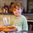 Adorable four year old boy celebrating his birthday and blowing — Stock Photo #43368323