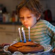 Adorable four year old boy celebrating his birthday and blowing — Stock Photo #43368377