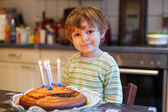 Adorable four year old boy celebrating his birthday and blowing — Stockfoto