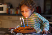 Adorable four year old boy celebrating his birthday and blowing — Photo