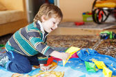 Funny boy of 4 years playing with paper ships at home — Stock Photo