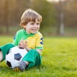 Blond boy of 4 playing soccer with football on football field — Stock Photo #43779805
