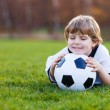 Blond boy of 4 playing soccer with football on football field — Stock Photo #43779871