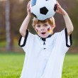 Blond boy of 4 playing soccer with football on football field — Stock Photo #43779905