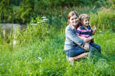 Little boy and his mother sitting on grass in summer forest — Stock Photo