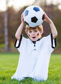 Blond boy of 4 playing soccer with football on football field — Stock Photo
