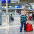 Little boy going on vacations trip with suitcase at airport — Stock Photo #43780669