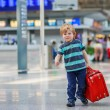 Little boy going on vacations trip with suitcase at airport — Stock Photo #43780727